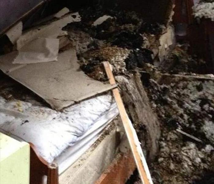 charred debris from fire on a bed