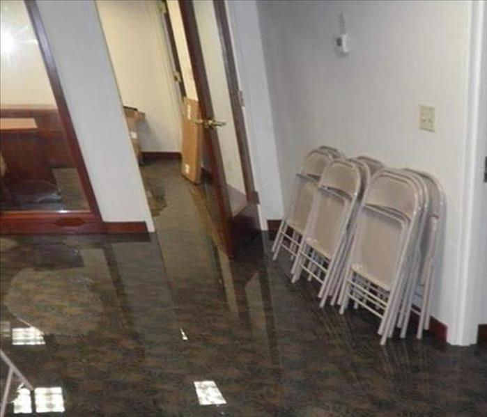 water with ceiling lights reflecting off carpeted office area, folding chairs leaning on wall