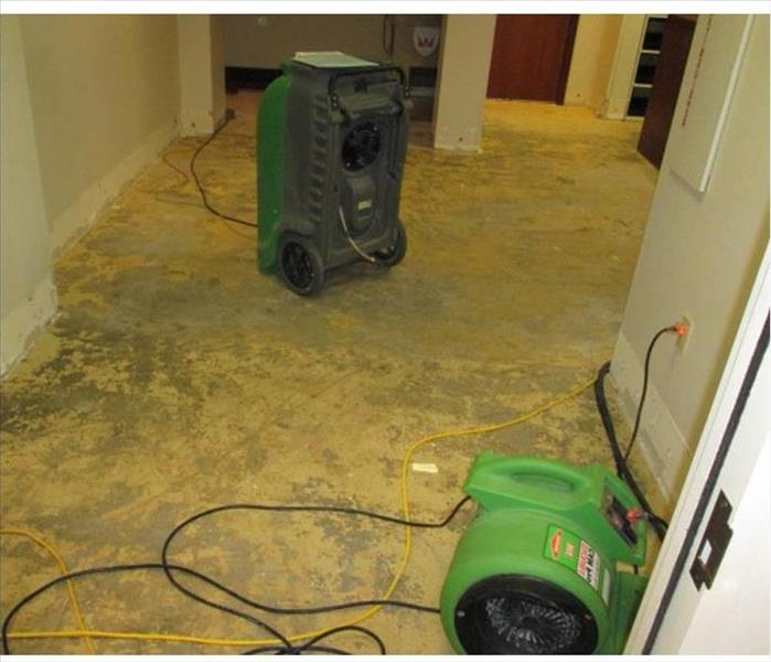 stripped floor to concrete pad, devices shown for drying